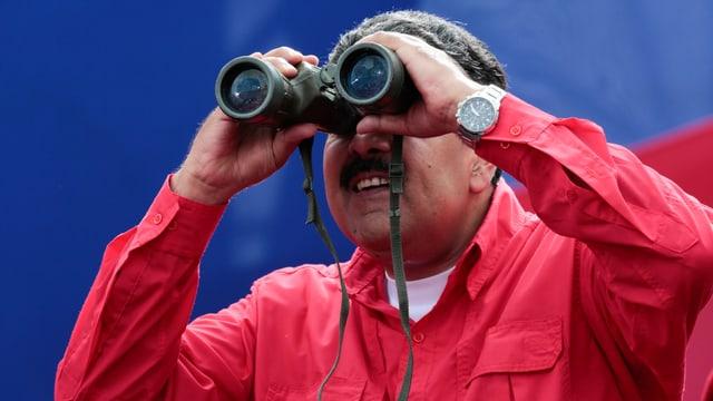 Maduro in rotem Hemd, schaut in ein Fernglas.