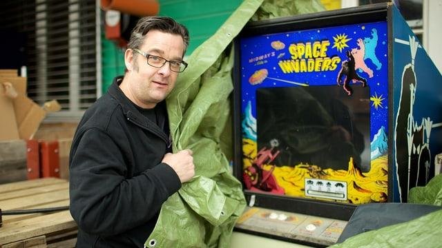 Ein Mann enthüllt einen alten, defekten Videospielautomaten im Freien