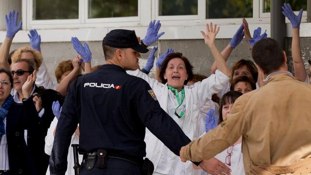 Spitalangestellte rufen und halten die Hände in die Hühe, davor bilden Polizisten eine Sperre.