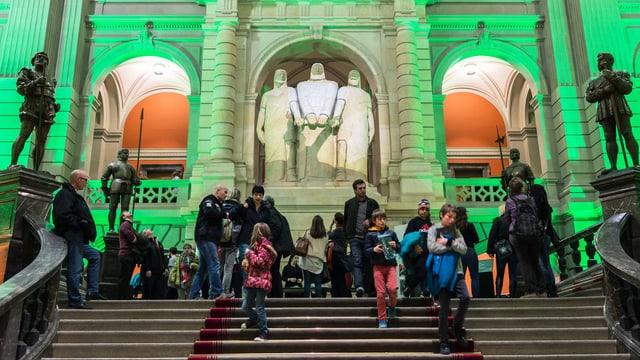 Besucher steigen die Treppe vor grün erleuchtete Statuen im Bundeshaus hinunter.