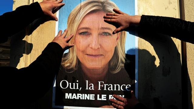 Unterstützer kleben Wahlplakate für Marine Le Pen in Frankreich.