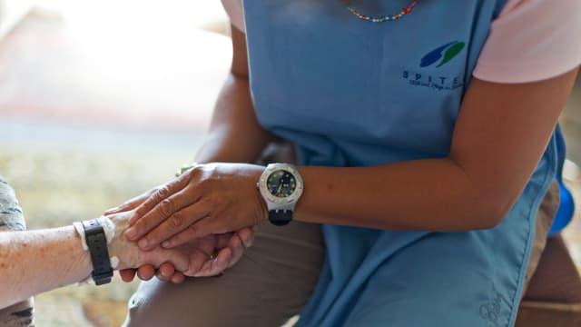 Eine Frau in einem Spitex-Kittel hält die Hand einer älteren Frau.