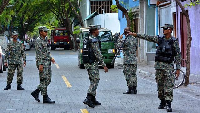 Fünf Soldaten patrouillieren in einer Strasse von Malé