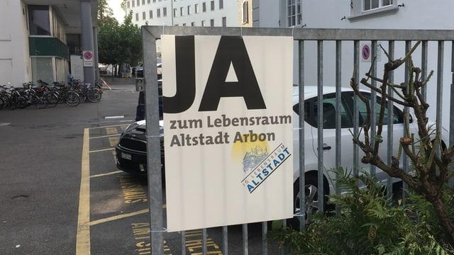 Plakat mit Ja-Parole hängt an einem Zaun