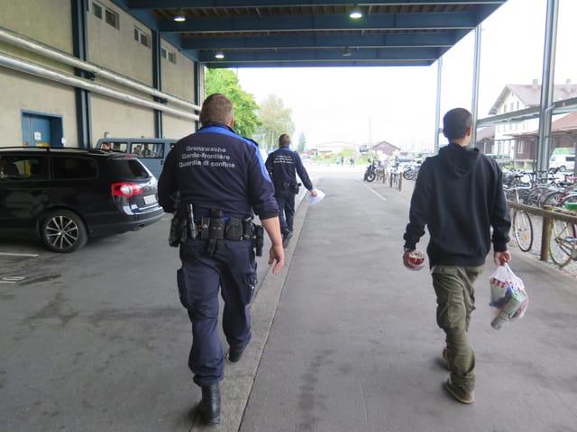 Zwei Grenzwächter und ein Flüchtling auf dem Weg ins alte Postgebäude.