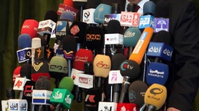 Viele bunte Mikrophone vor Rednerpult
