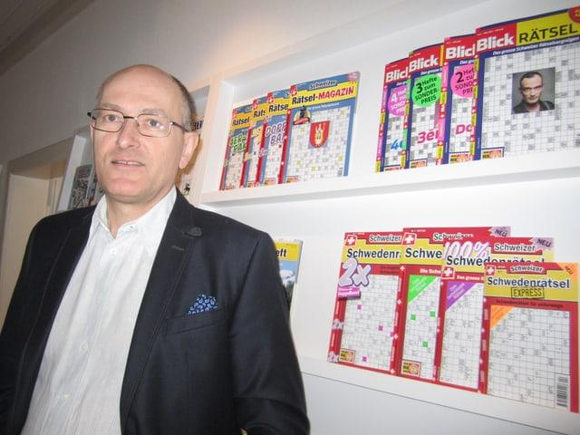 Rätselchef Thomas Küng vor einer Auswahl seiner Titel.