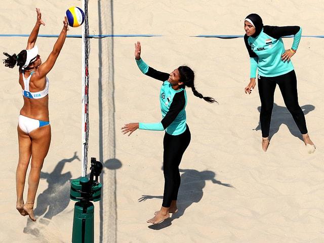 Die ägyptischen Beachvolleyballerinnen in langen Kleidern, eine mit Kopftuch, die Deutschen im Bikini, am Netz.