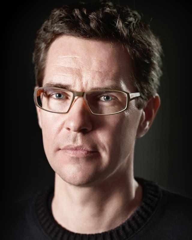 Porträt von einem Mann mit Brille und schwarzem Pullover.