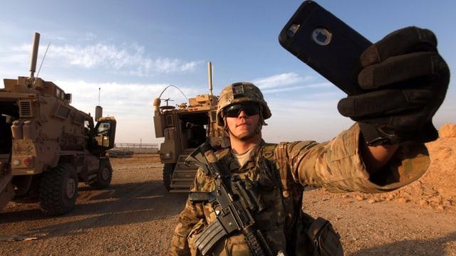 Soldat macht ein Selfie, im Hintergrund zwei gepanzerte Fahrzeuge.