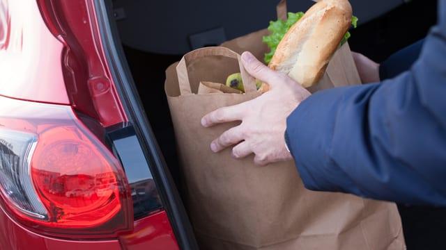 Eine Person stellt eine braune Tüte mit Lebensmitteln darin in den Kofferraum eines roten Autos (oder nimmt die Tüte heraus)