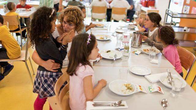 Kinder und Betreuerinnen essen in einem Hort in Zürich ihr Mittagessen.