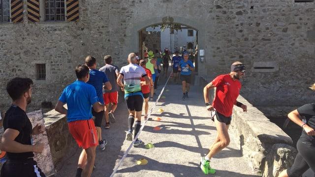 Läufer, die ins Schloss hinein rennen, daneben Läufer, die aus dem Schloss herauskommen