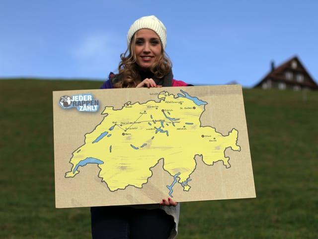 Florence Fischer hält ein Schild mit einer Schweizerkarte
