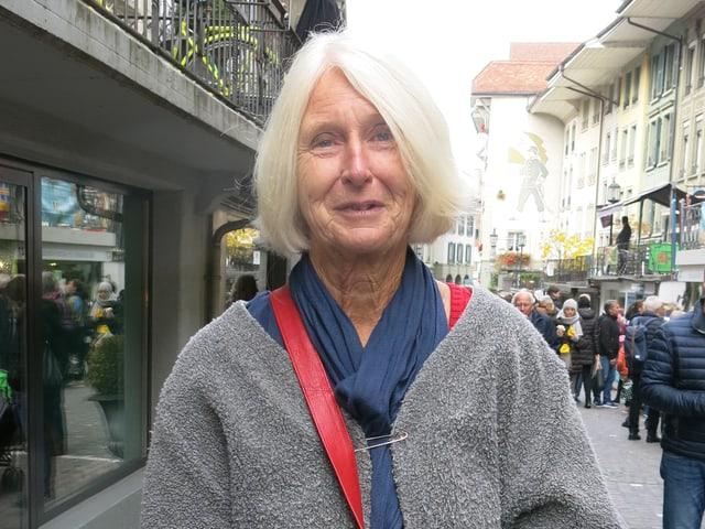 Ältere Frau mit weissblondem Haar. Trägt einen grauen Mantel, einen blauen Schal und eine rote Tasche.