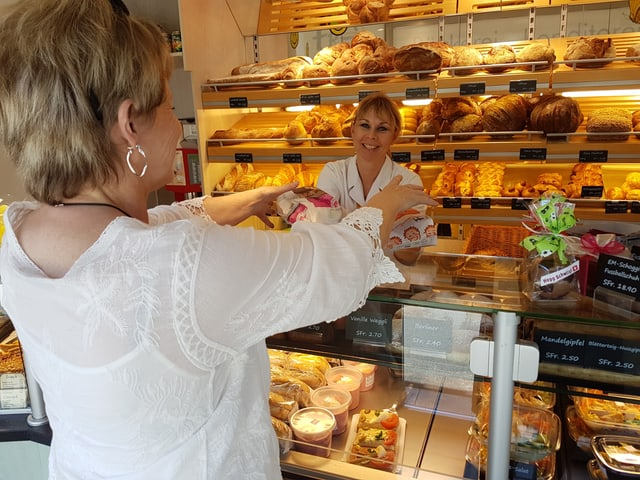 Kundin nimmt am Tresen in der Bäckerei von der Verkäuferin Brot entgegen.