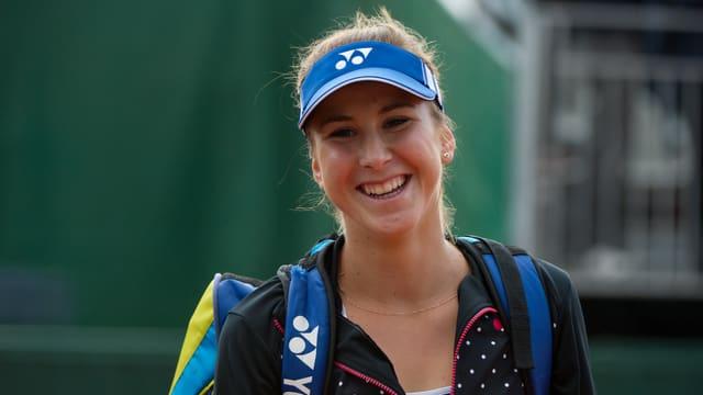 Belinda Bencic lacht mit Käppi und geschulterter Tennistasche.