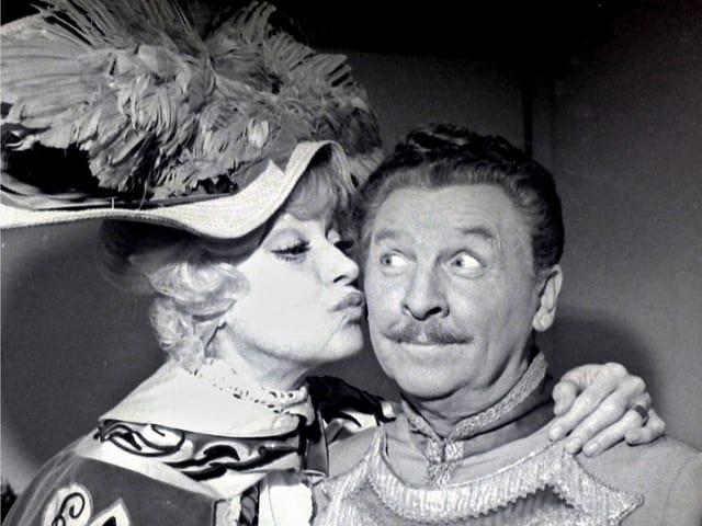 Carol küsst Eddie auf die Wange. Das Foto wurde Backstage während einer Vorstellung am Broadway aufgenommen. Beide Darsteller tragen ihre Kostüme: Carol Channing einen pompösen Federhut und Eddie Bracken eine Livrée.
