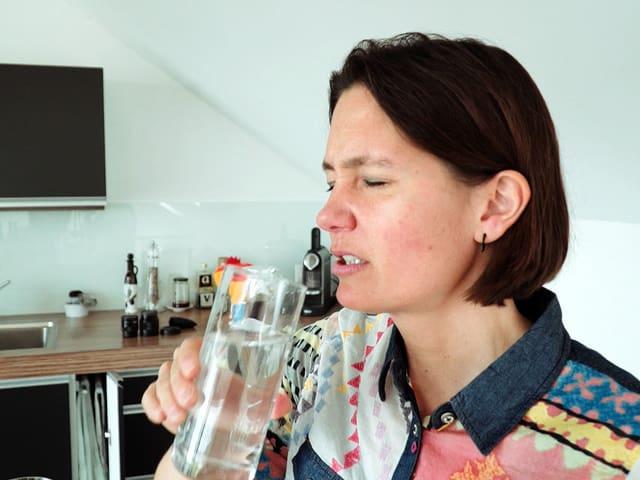 Frau hält ein Wasserglas in der Hand und rümpft die Nase