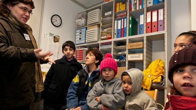 Eine Seelsorgerin spricht mit einer sechsköpfigen Asylbewerberfamilie in einem Büro.