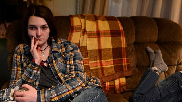 Eine Teenagerin sitzt mit ernstem Gesicht auf einer Couch