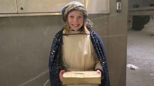 Mädchen mit goldener Schachtel als Spendenkasse