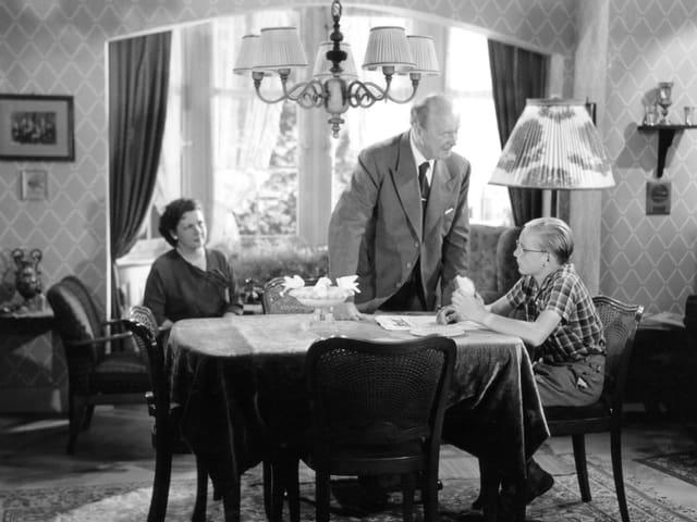 Ein blonder Jugendlicher sitzt an einem Tisch und hält ein belegtes Brot in der Hand. Am anderen Tischenden sitzt eine Frau und blickt zu ihm hinüber. Neben dem Jungen steht ein älterer Mann und scheint auf ihn einzureden.