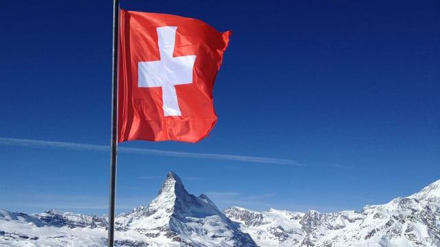 Schweizer Fahne weht, im Hintergrund das Matterhorn.