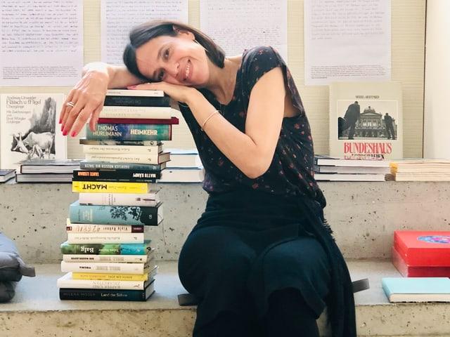 Annette König neben einem Stapel Bücher