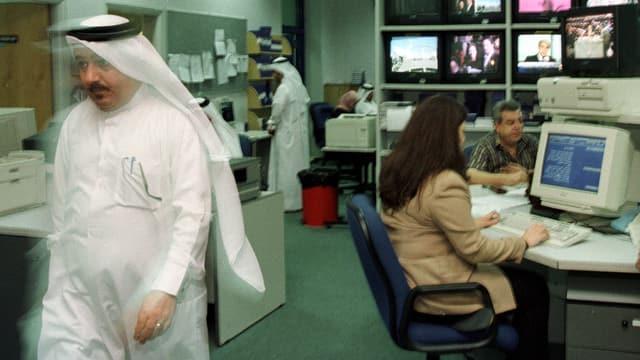 Büroszene, zwei Männer in weissem, saudischen Gewand, eine Frau vor einem Computer.