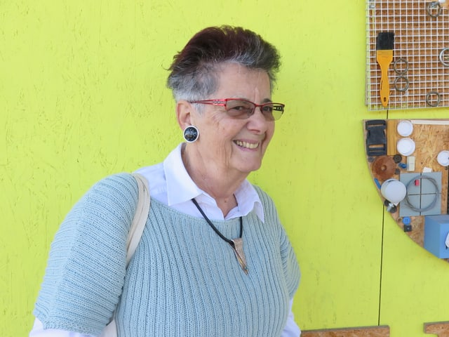 Die aufgestellte Seniorin mit dem Kurzhaarschnitt lächelt in die Kamera