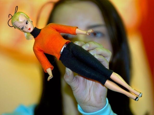 Barbie mit rotem Pulli und schwarzem Rock in der Hand einer Frau.
