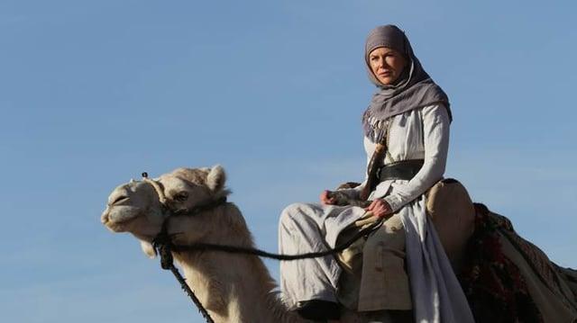 Kidman mit Kopftuch auf einem Kamel.