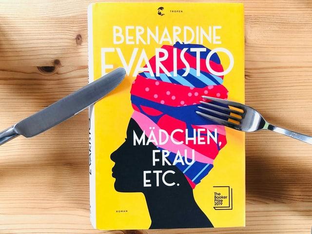 «Mädchen, Frau etc.» von Bernardine Evaristo liegt auf einem Kiefernbrett