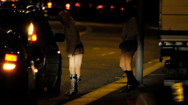 Zwei Prostituierte am Strassenrand, ein Freier im Auto hält.