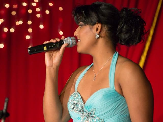 Die dunkelhaarige Sängerin trägt ein türkisfarbenes Abendkleid.