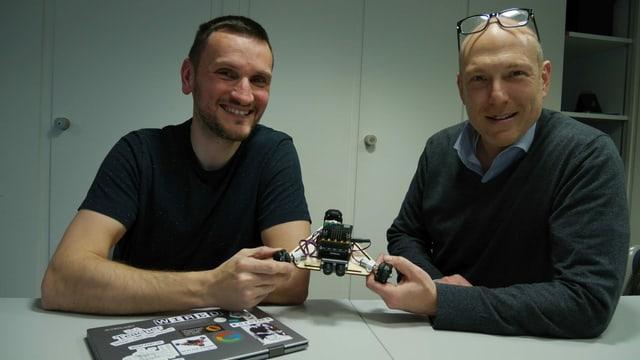 Zwei Männer sitzen an einem Tisch und halten einen kleinen Roboter in den Händen