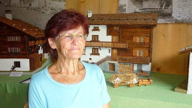 Maria Cavegn davant ina da las chasas en miniatura.