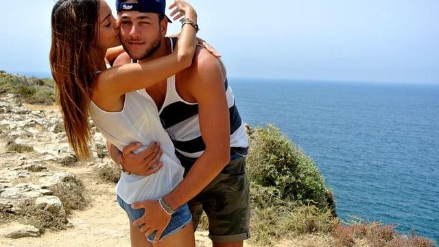 Die Miss Schweiz und ihr Freund auf einer Klippe beim Meer.
