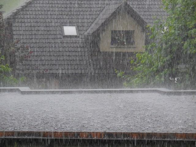 Blick aus einem Fenster. Das gegenüberliegende Haus sieht man vor lauter Regen kaum noch.