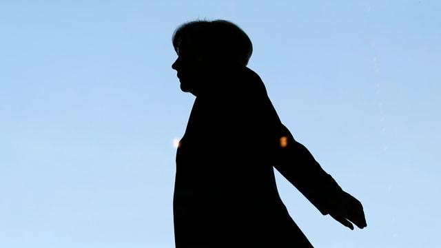 Die Silhouette der deutschen Bundeskanzlerin Angela Merkel, die Hände nach hinten ausgestreckt.