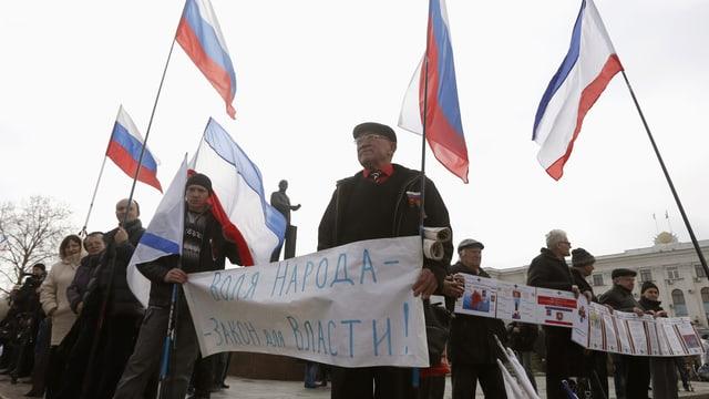 Demonstranten mit russischen Flaggen demonstrieren.