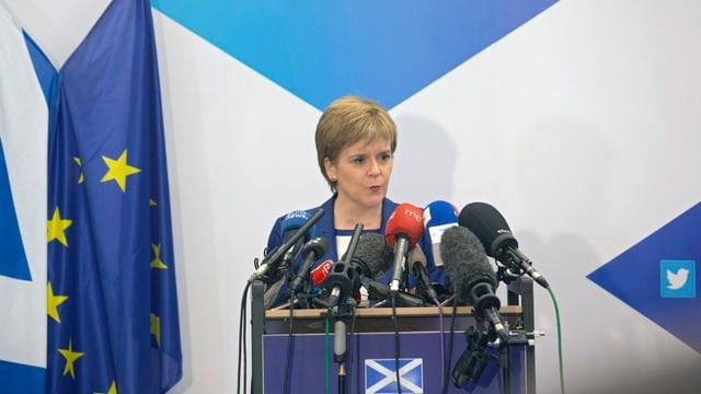 Sturgeon steht an einem Rednerpult und spricht in Mikrofone, daneben die schottische und die EU-Flagge.