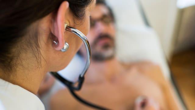 Ärztin untersucht Patienten. Man sieht ihren Kopf samt Stetoskop von hinten, scharf und nahe. Im Hintergrund sieht man einen Mann liegen.