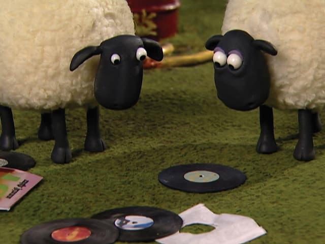 Zwei Schafe aus Knetmasse schauen auf eine Vinyl-Platte.