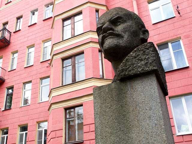 Leninbüste vor einer pinken Hausfassade.