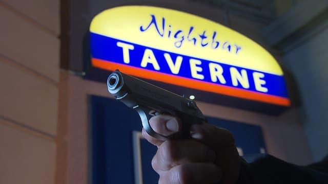 Eine Person hält eine Pistole vor einem Cabaret-Eingang.