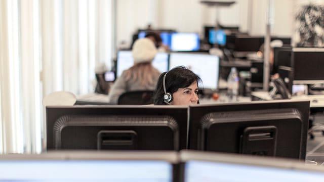 Eine Frau sitzt hinter zwei Bildschirmen in einem Grossraumbüro.
