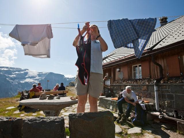Eine Frau hängt an einer Wäscheleine vor einer SAC-Hütte ein Badekleid auf.