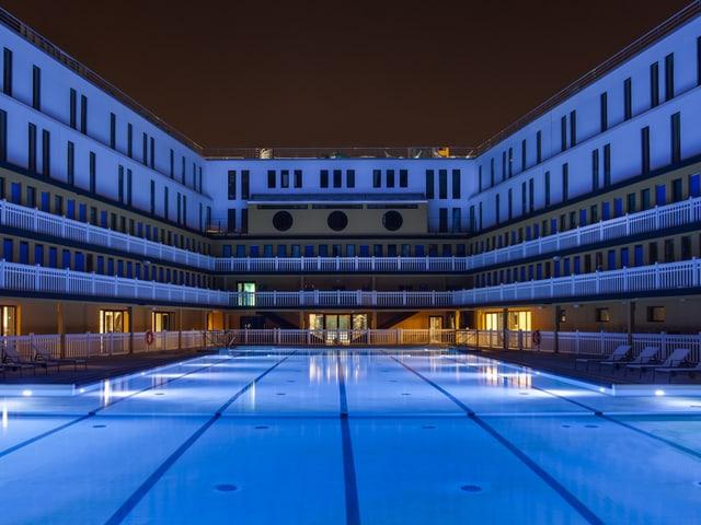 Schwimmbecken, umgeben vom Garderobengebäude bei Nacht.